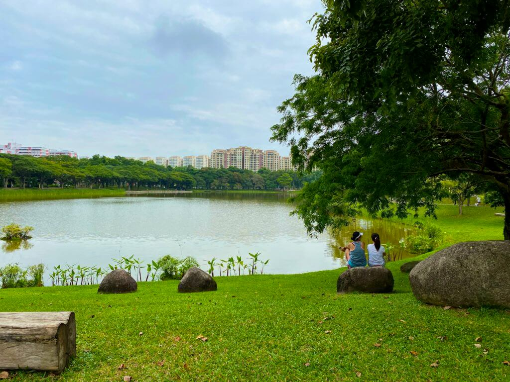 two people sitting on a rock in a park